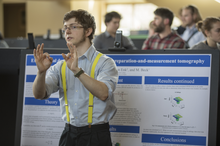 Physics major Aidan McCormick '17 in front of his poster on quantum state tomography, or the process of characterizing a quantum optical system.