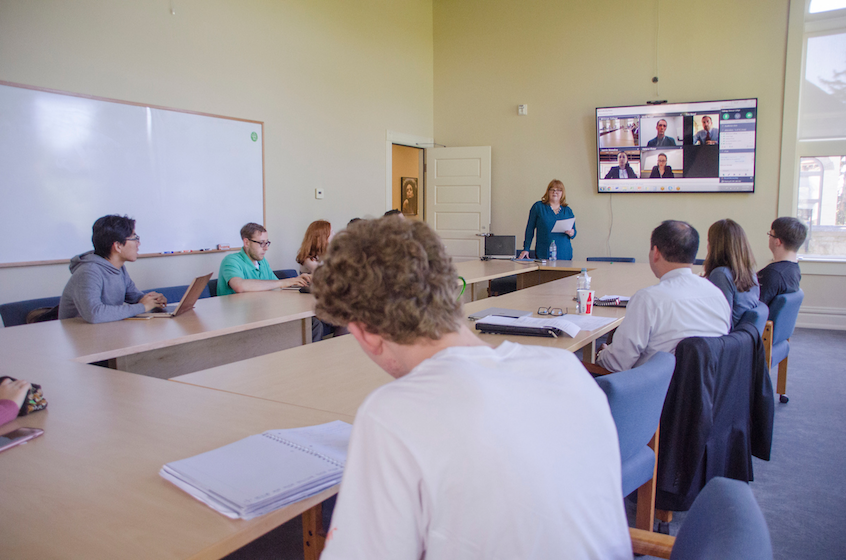 Whitman students learn about banking and finance opportunities in a video conference with alumni, as Kimberly Rolfe (standing), director for business engagement at Whitman, moderates.