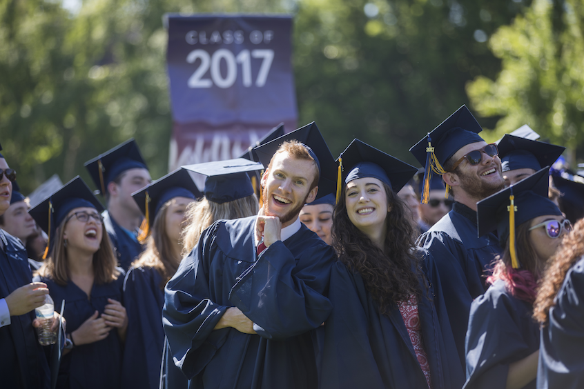 Economics and psychology major Spencer Mueller '17 (center left) poses with classmates at Commencement.