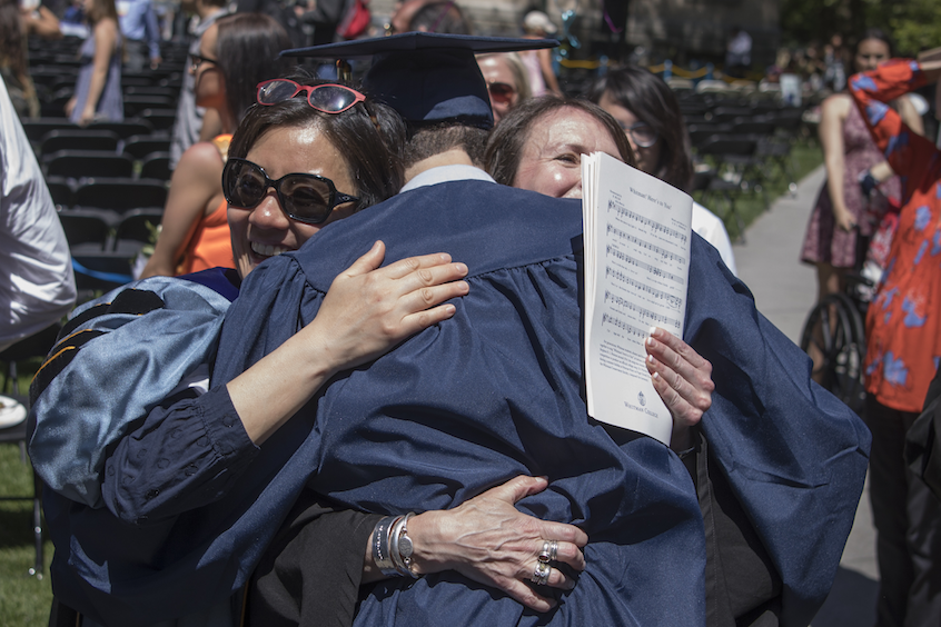 Associate Professor of Sociology Helen Kim (left) and Associate Professor of Anthropology and Interdisciplinary Studies Suzanne Morrissey hug a newly-minted Whitman graduate.