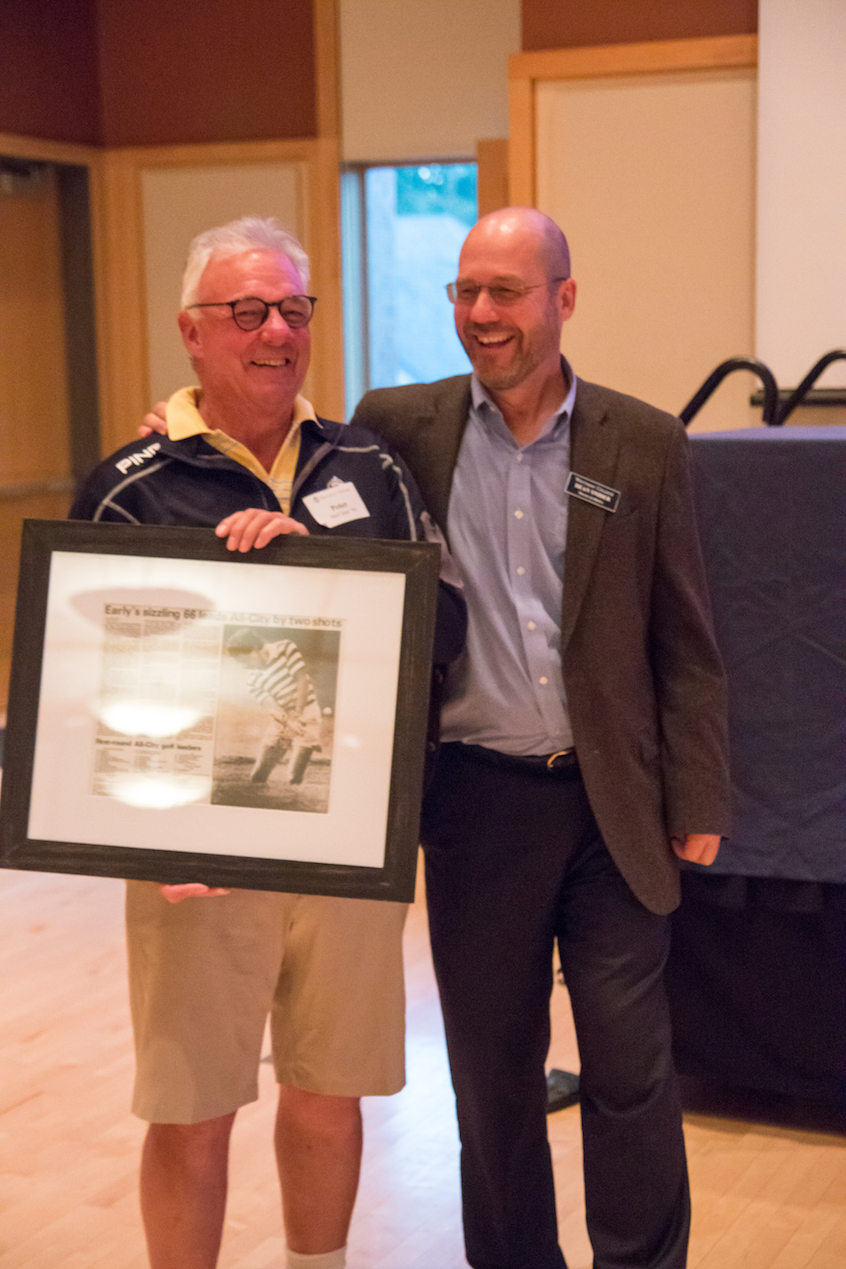 "Men's Golf Coach Peter McClure '93 accepts a framed article from the ""Union-Bulletin"" from Athletics Director Dean Snider. McClure has announced his retirement following this season, his 25th."