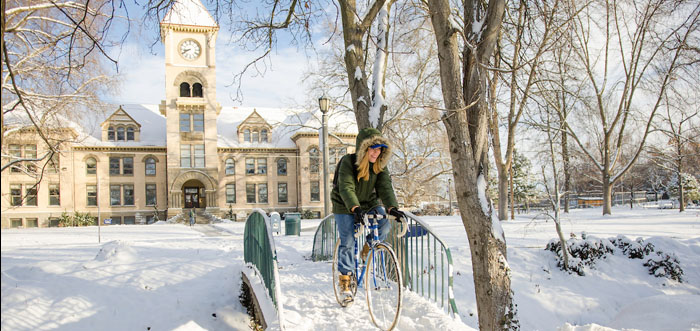 Student riding bike in the snow