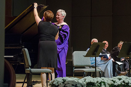 President Kathleen Murray offers Assistant Director of Alumni Relations Jennifer Northam a musical hand during the Presidential Installation ceremony.