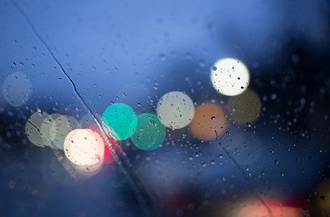 Raindrops on a window pane enhance the season of lights.