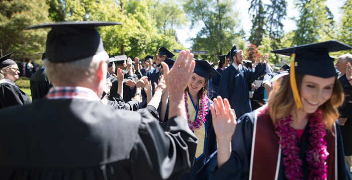 50th Reunion Class and graduates share high fives.