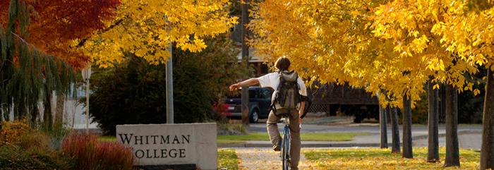 Whitman student riding bike next to Whitman College sign