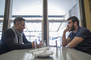 Author Alexander Maksik '95 (left) and Bashar Haidar '20 share a meal at Walla Walla's Olive Market Place & Cafe.