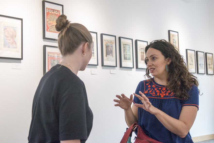 Jennine Capó Crucet (right) tours the Stevens Gallery, currently showcasing work by artist Paul Valadez, in Whitman's Reid Campus Center.