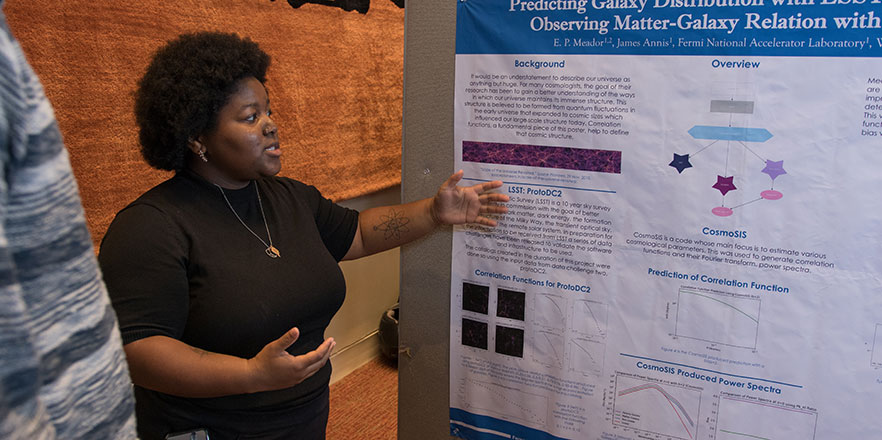 A student presents her poster at the Undergraduate Conference.