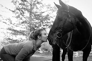 Cello Lockwood kisses a horse on the nose.