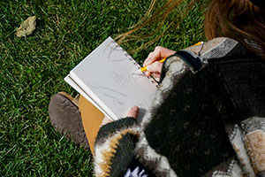 A student sketches a tree in a notebook.