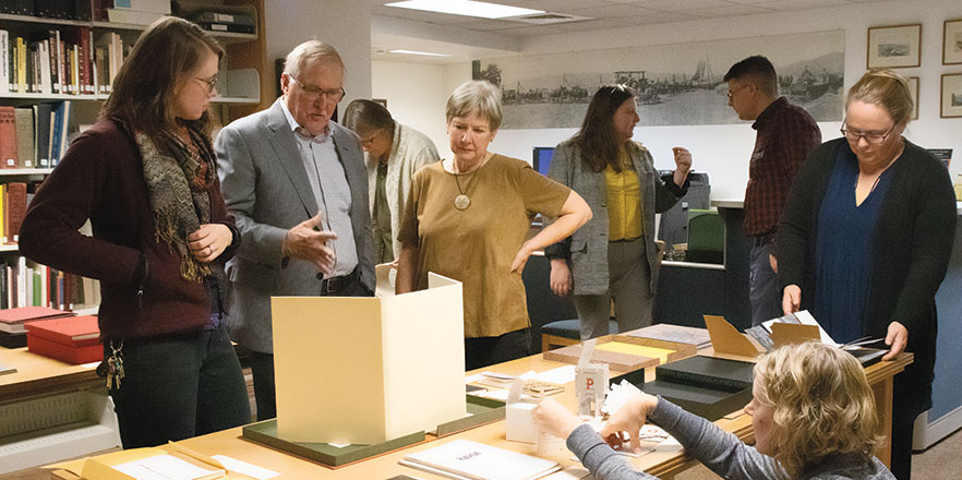 Peter Newland '67, center, and his wife, Robyn Johnson, right, talk with Antonia Keithahn, assistant director of Disability Support Services, about their donation of artists' books during an open house in the Penrose Library.