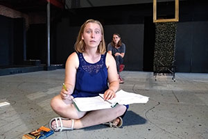 A student works on a play on stage.