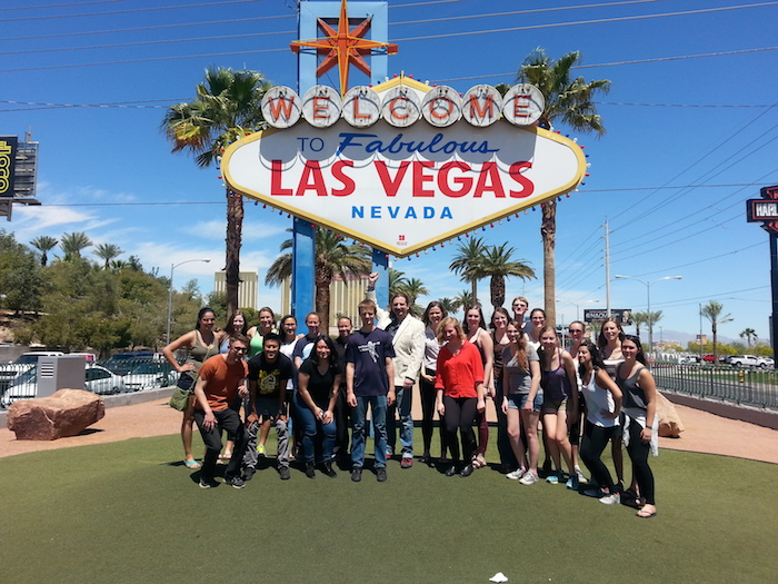 Group of students stand around Las Vegas welcome sign