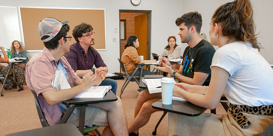 Matt Bost has a discussion in a rhetoric course with three students.