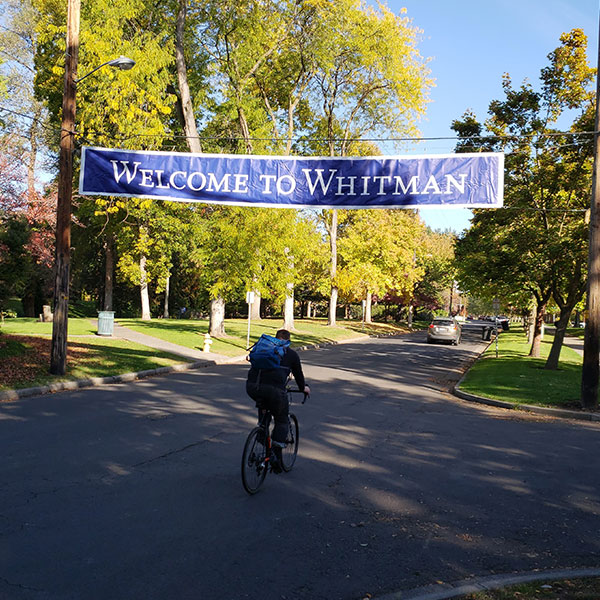 Welcome to Whitman College banner with bicyclist riding underneath