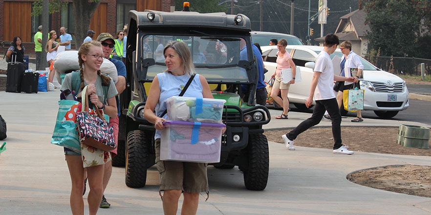 A student and her mother carry items during move-in.