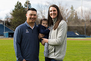Brian and Kirsten Kitamura hold their baby while standing in a baseball field.