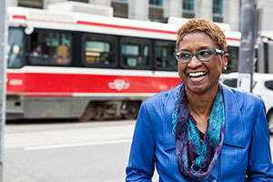 Paula Boggs smiles in front of a transit bus.