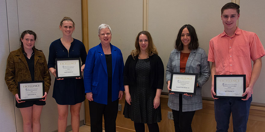 Four students stand with President Kathleen Murray and writer Sarah Kendzior with their award plaques.