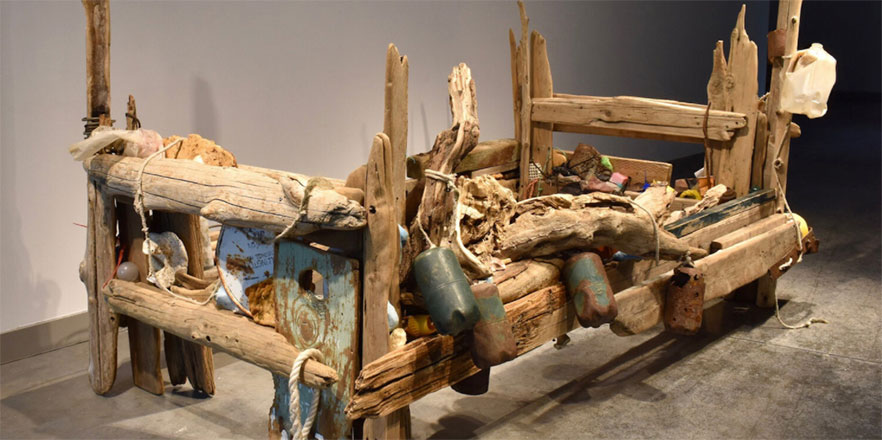 A piece from Tess Francavilla's senior thesis — mixed media wooden bed frame, sanded and artifically weathered, driftwood, rusted metal, trash gathered along the Columbia River.