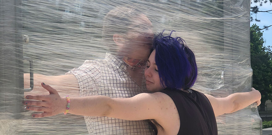 Two people hug with a sheet of plastic wrap between them.