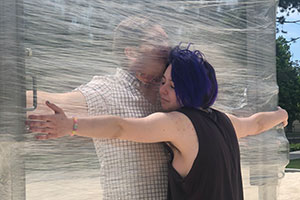 Two people hug with a wall of cellophane between them.