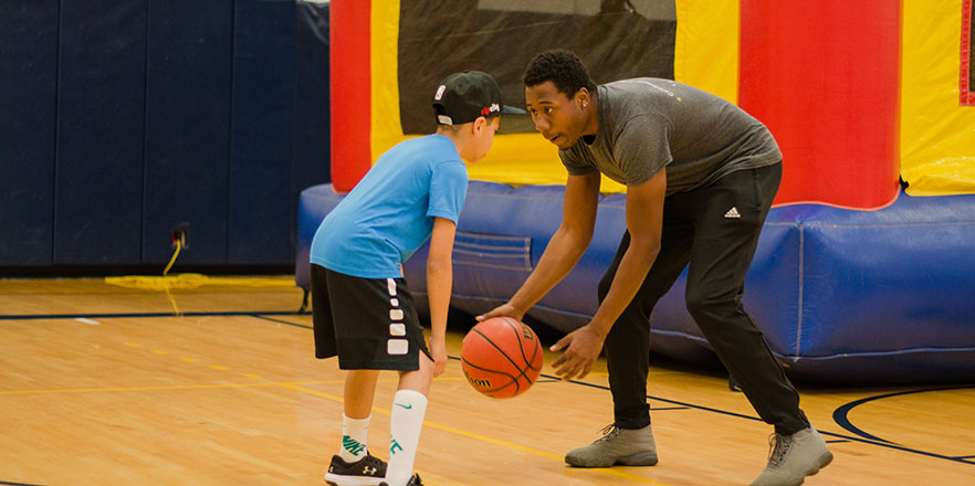 A Whitman student plays basketball with an elementary school student.