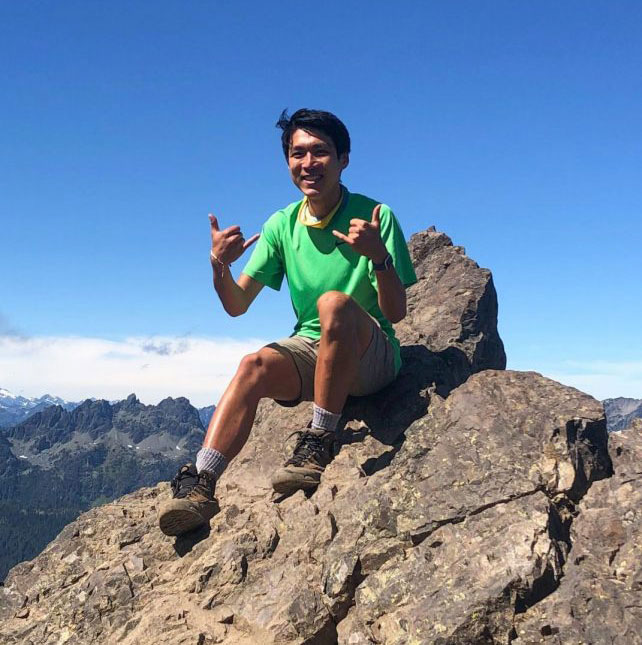 Jake Wang smiles atop a mountain