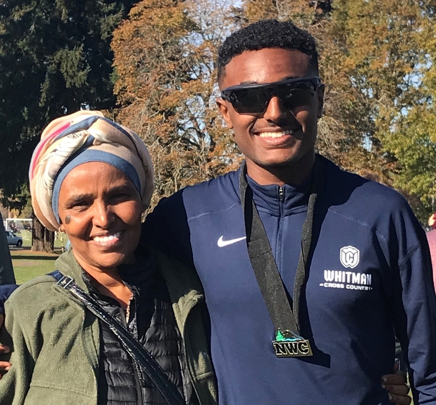 Saleh and his mom smile for a photo at the cross country team's conference race held in Walla Walla.