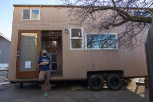 Preskenis stands outside the tiny house he built