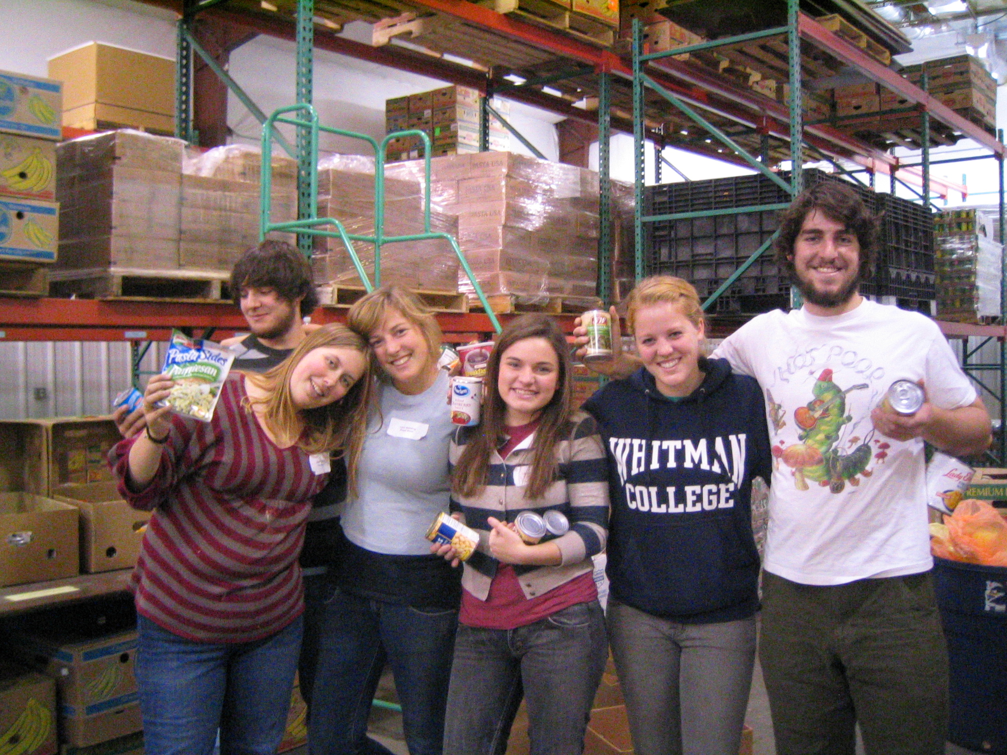 Students posing with cans of food they sorted at food bank.