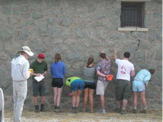 students examine the rocks sin the wall of the Kent Mercantile Building. (Photo by Matthew Morriss)