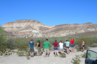 In the Bofecillos volcanic field, students take notes on Three Dike Hill.  Here three feeder dikes fed the basalt flow atop numerous tuffs.  (Photo by Matthew Morriss)